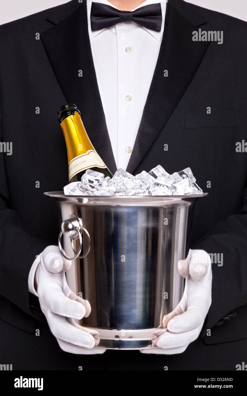 Waiter holding a wine cooler with a bottle of Champagne on ice - Stock Image