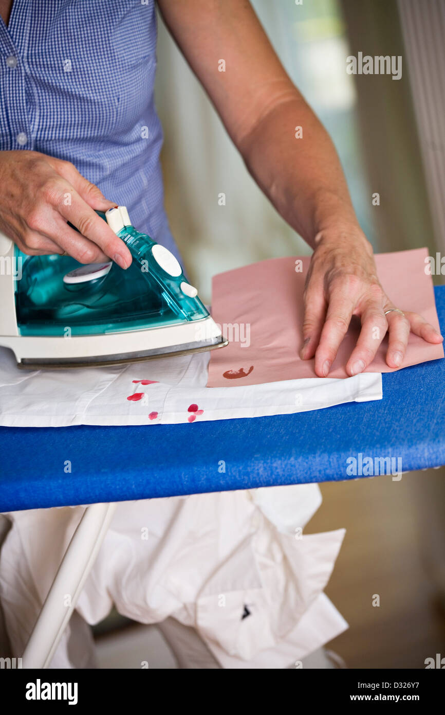 Woman removing wax by ironing - Stock Image