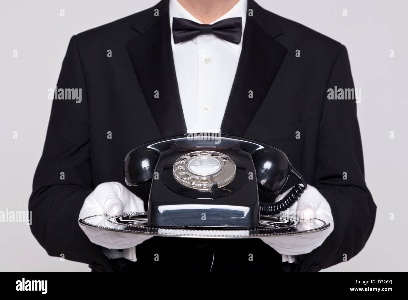 Butler holding a silver tray with an old retro black telephone on it. - Stock Image