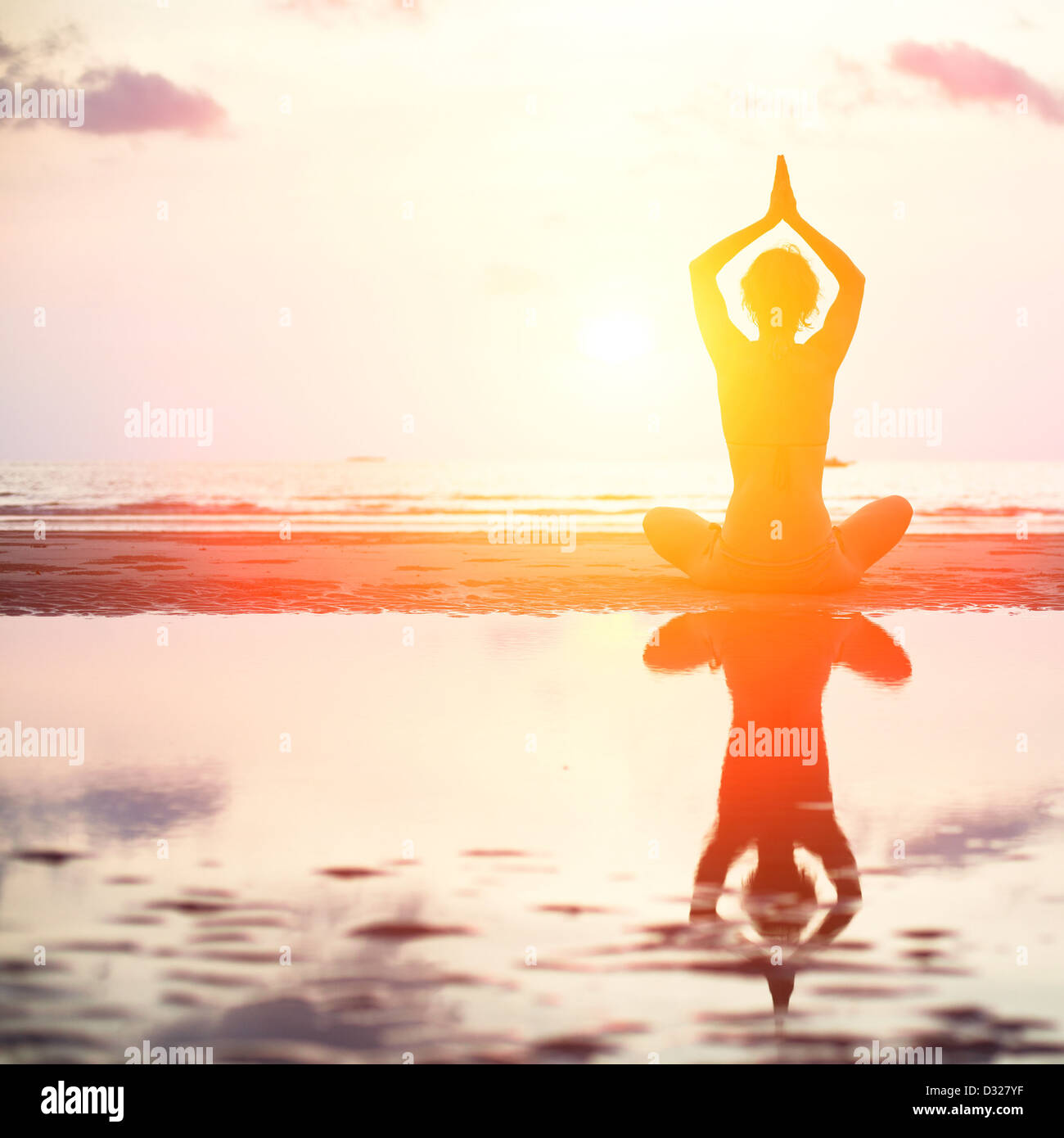 Yoga woman sitting in lotus pose on the beach during sunset, with reflection in water (in bright colors) - Stock Image