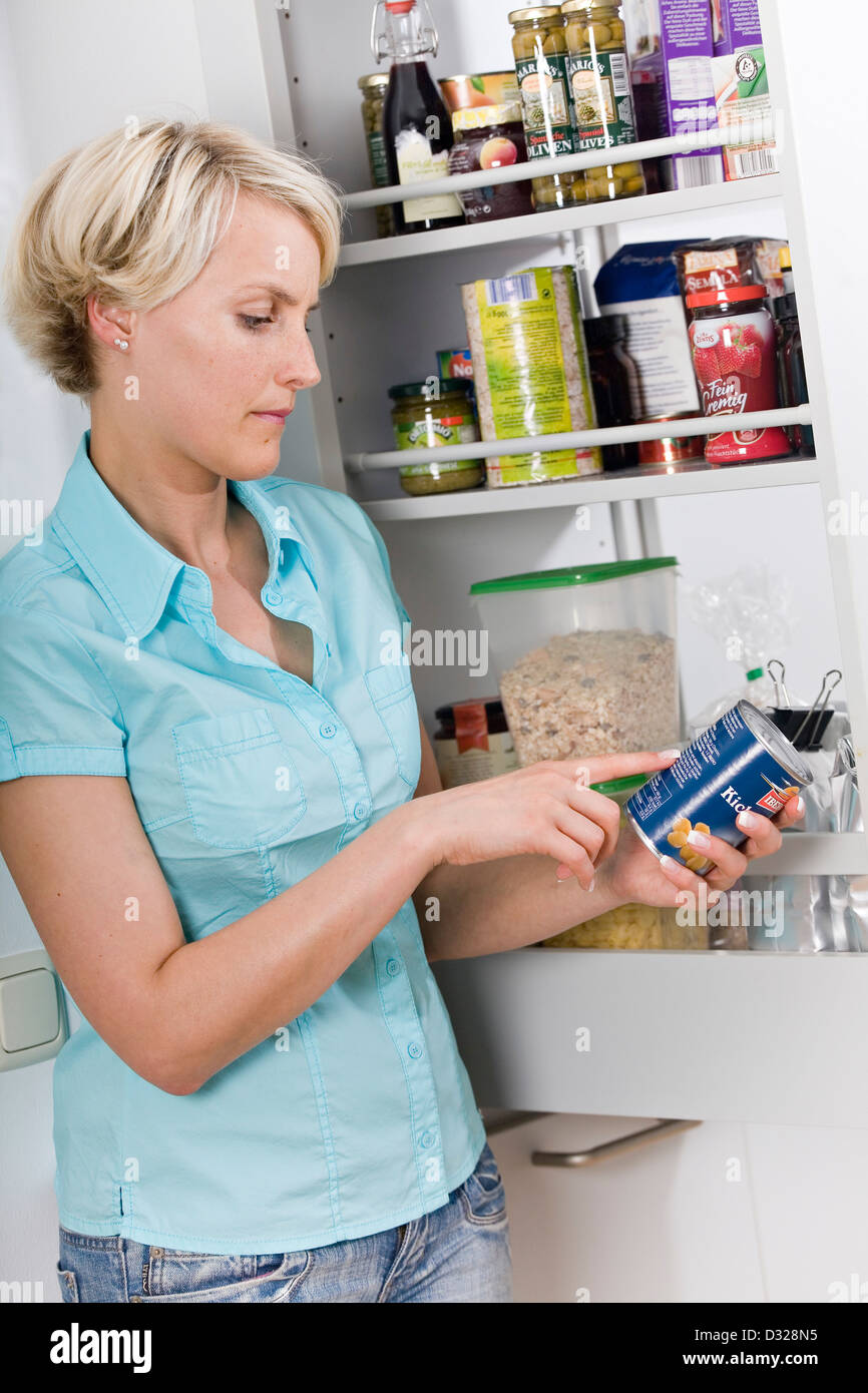 Woman checking best-before date - Stock Image