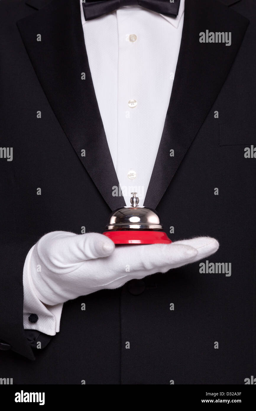 Waiter in black tie and white gloves holding a service bell. - Stock Image
