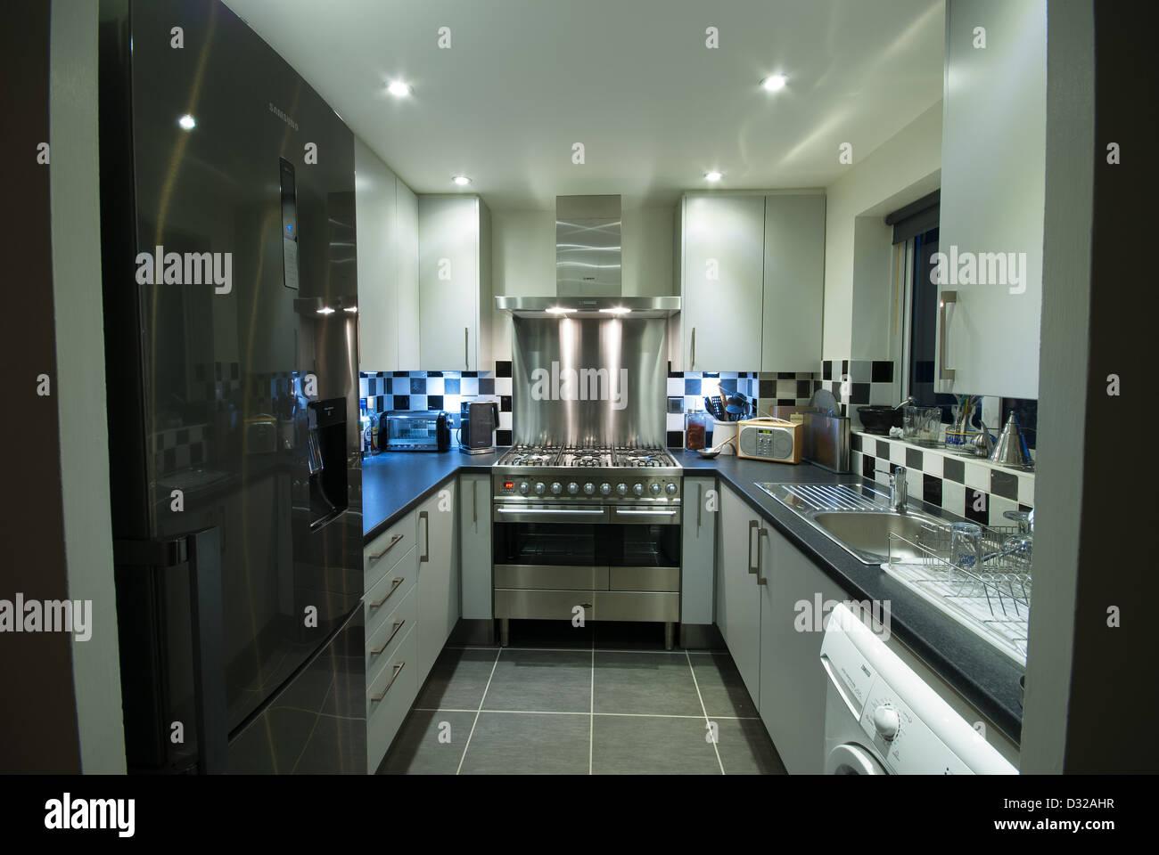 a small, modern domestic kitchen with a fridge-freezer, washing