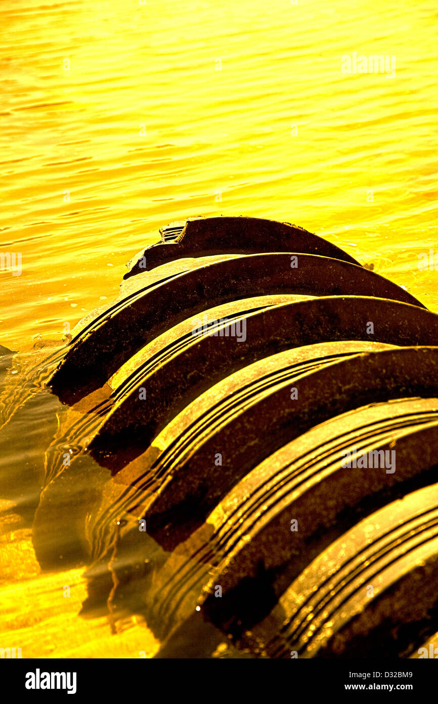 A beautiful golden glow surrounds this usually mundane object of a water pipe leading into the ocean. - Stock Image