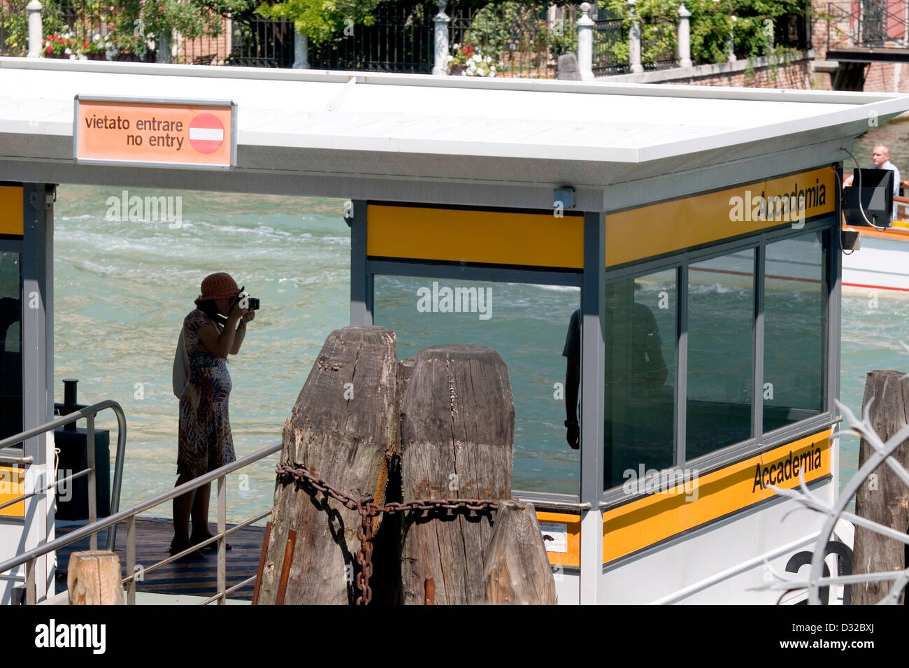 A tourist taking a picture on the Accademia vaporetto (water-bus) stop, Dorsoduro, Venice, Italy. - Stock Image