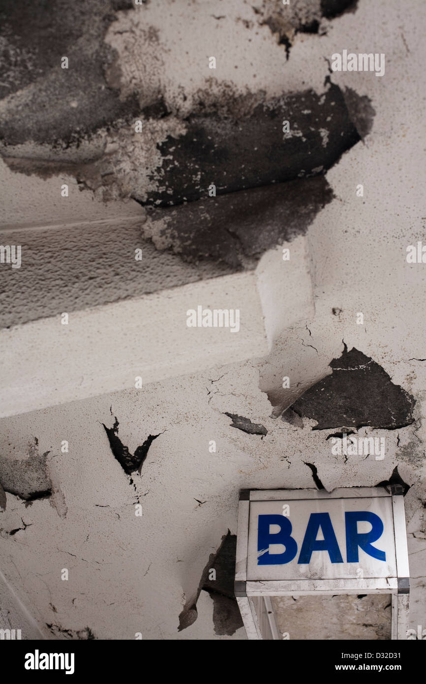 A sign for a bar below a concrete awning on a neglected building. - Stock Image