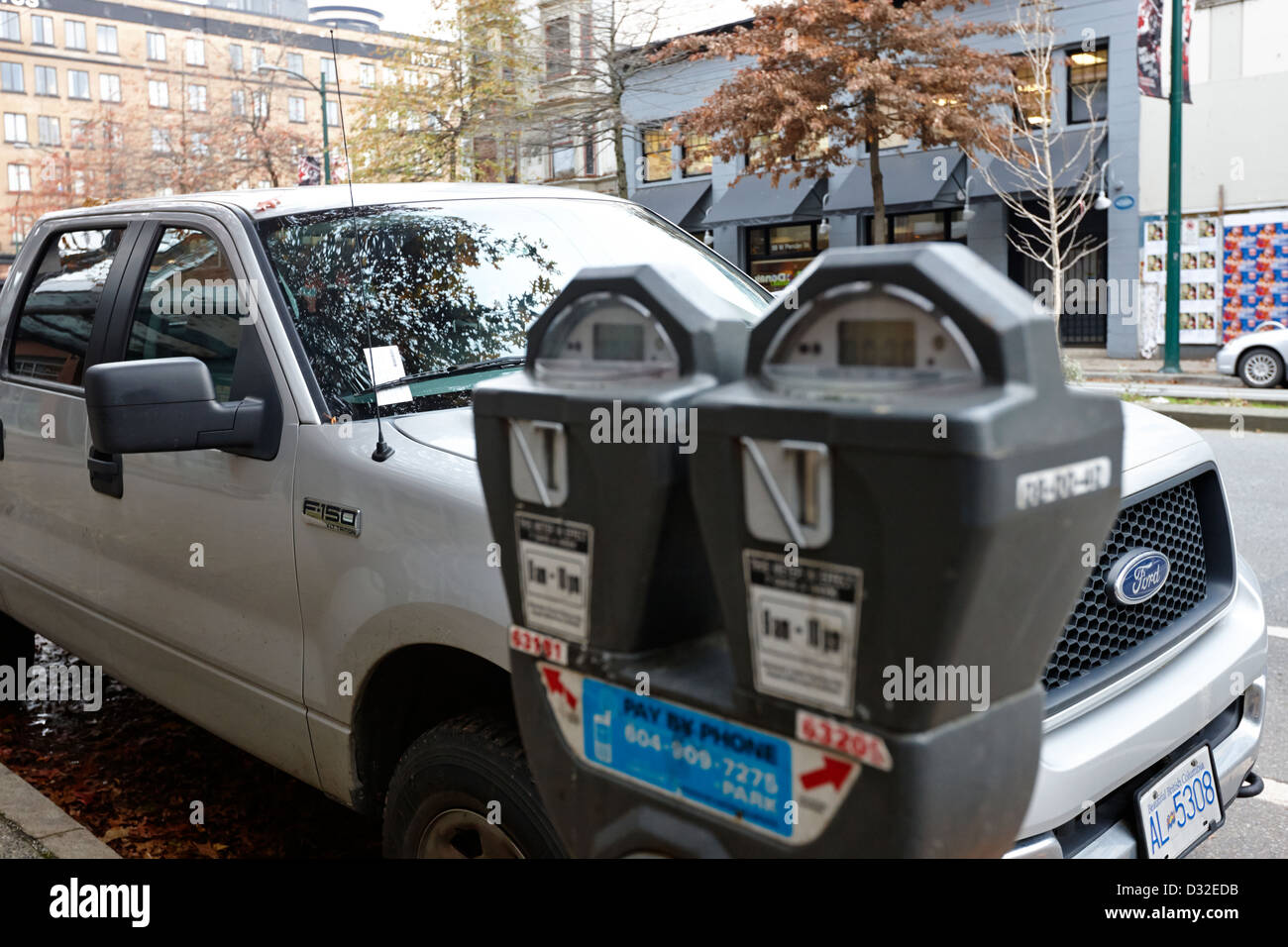 vehicle with parking ticket parked onstreet beside expired parking meter Vancouver BC Canada - Stock Image