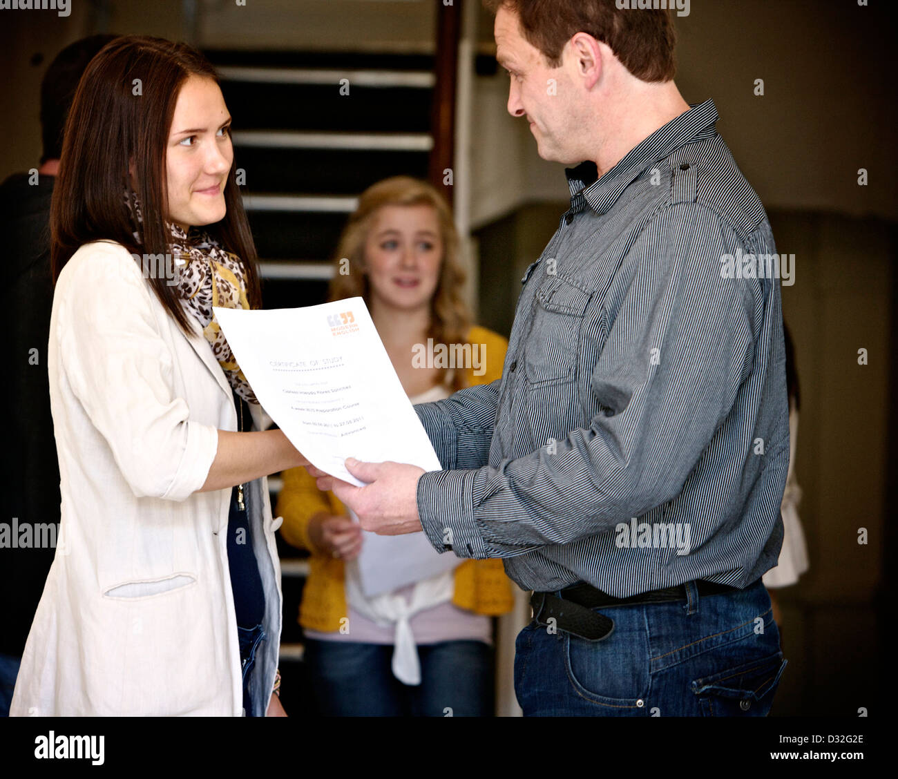 A young person being presented with their college degree having graduated - Stock Image