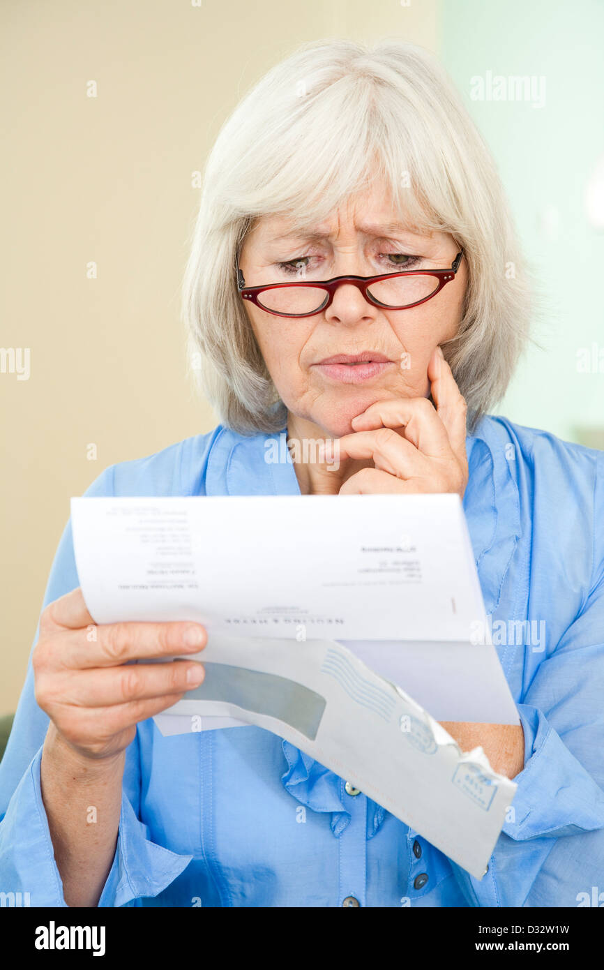 Elderly lady reading an official letter - Stock Image
