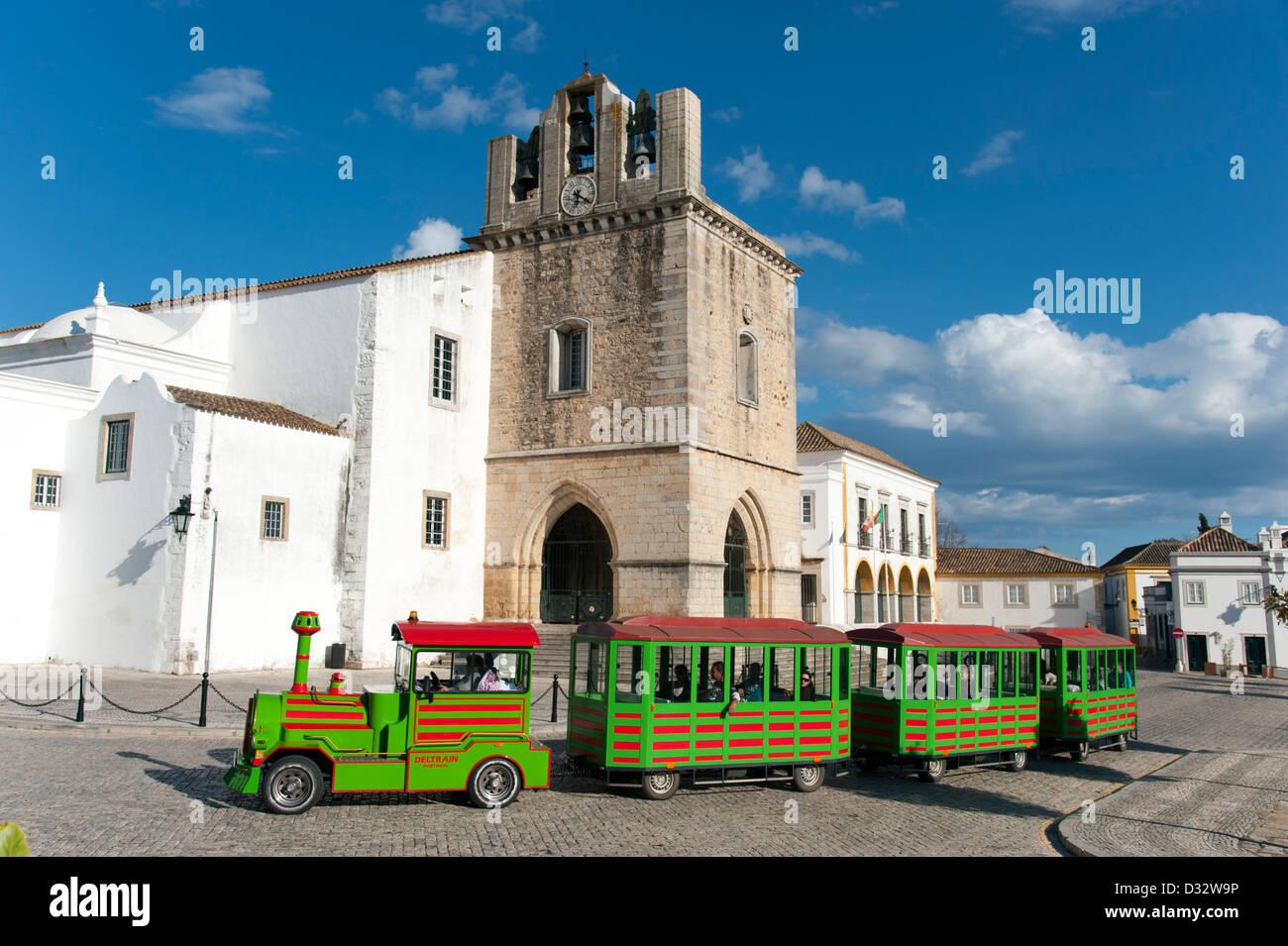 Tourist fun train going past Faro Cathedral, Portugal - Stock Image