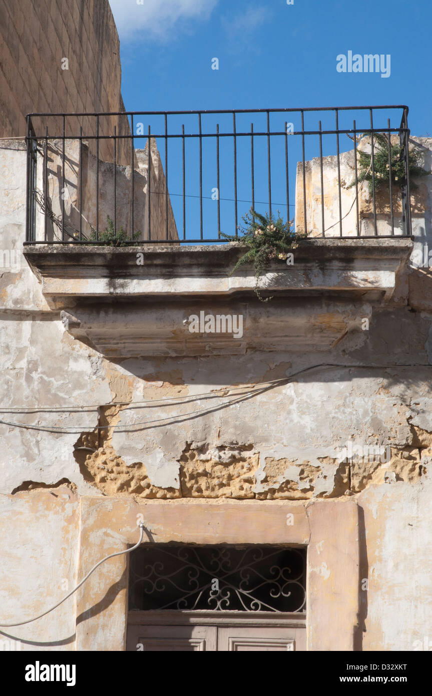 Gozo, street scene,  peaceful, no people, no traffic, stone walls, stone slab , balcony, old door, peeling paintwork - Stock Image