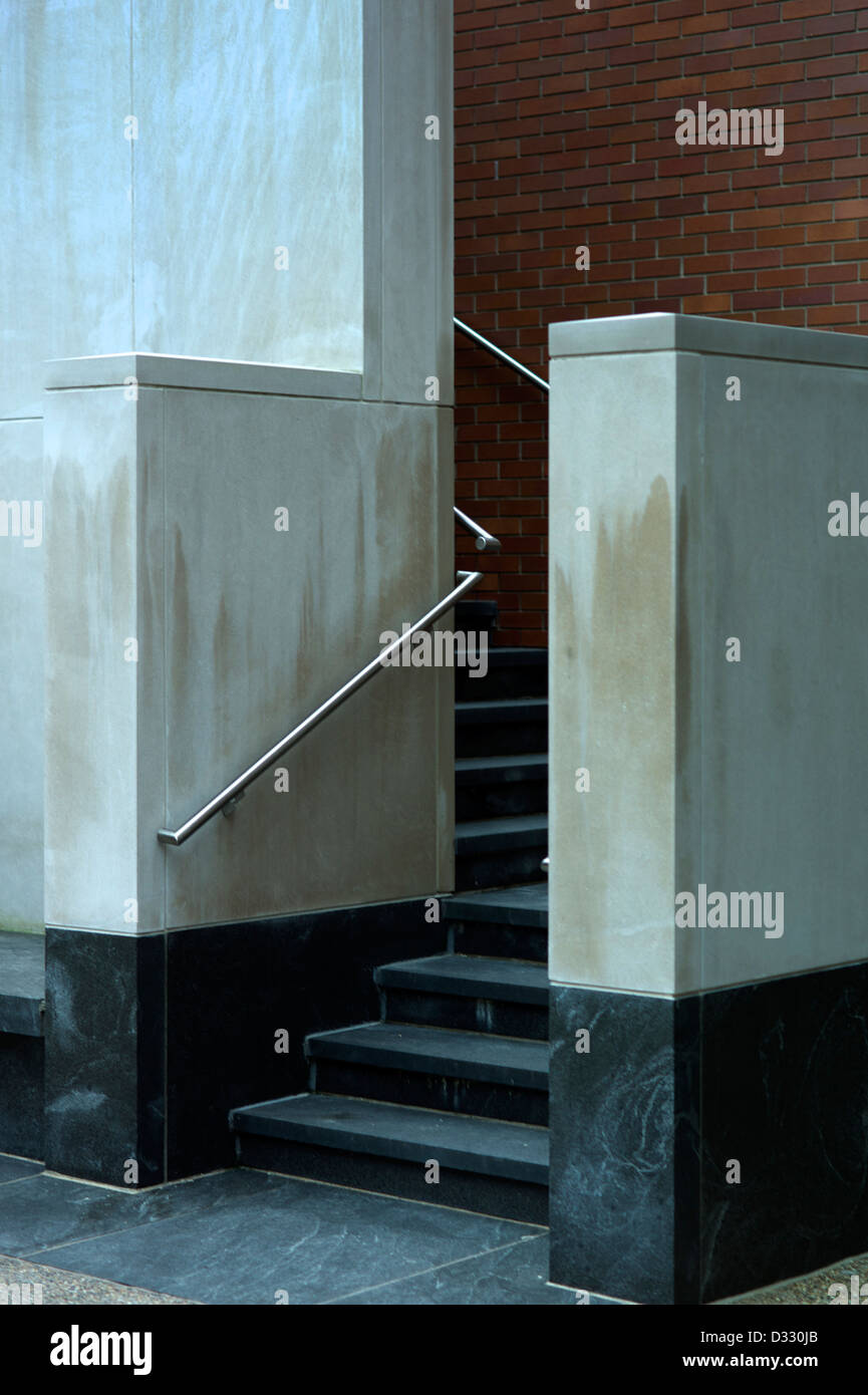 Stairs leading to an industrial building with brick wall. - Stock Image