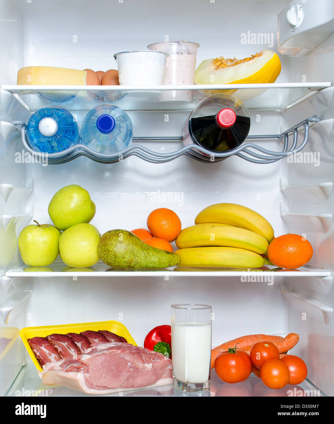 Open fridge full of fruits, vegetables and meat with marked calories - Stock Image