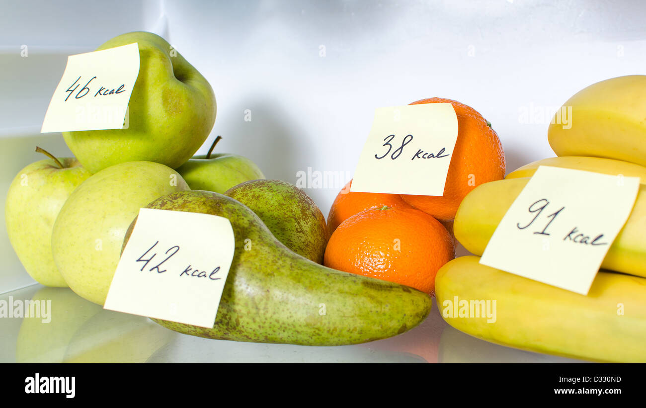 Open fridge full of fruits with marked calories - Stock Image