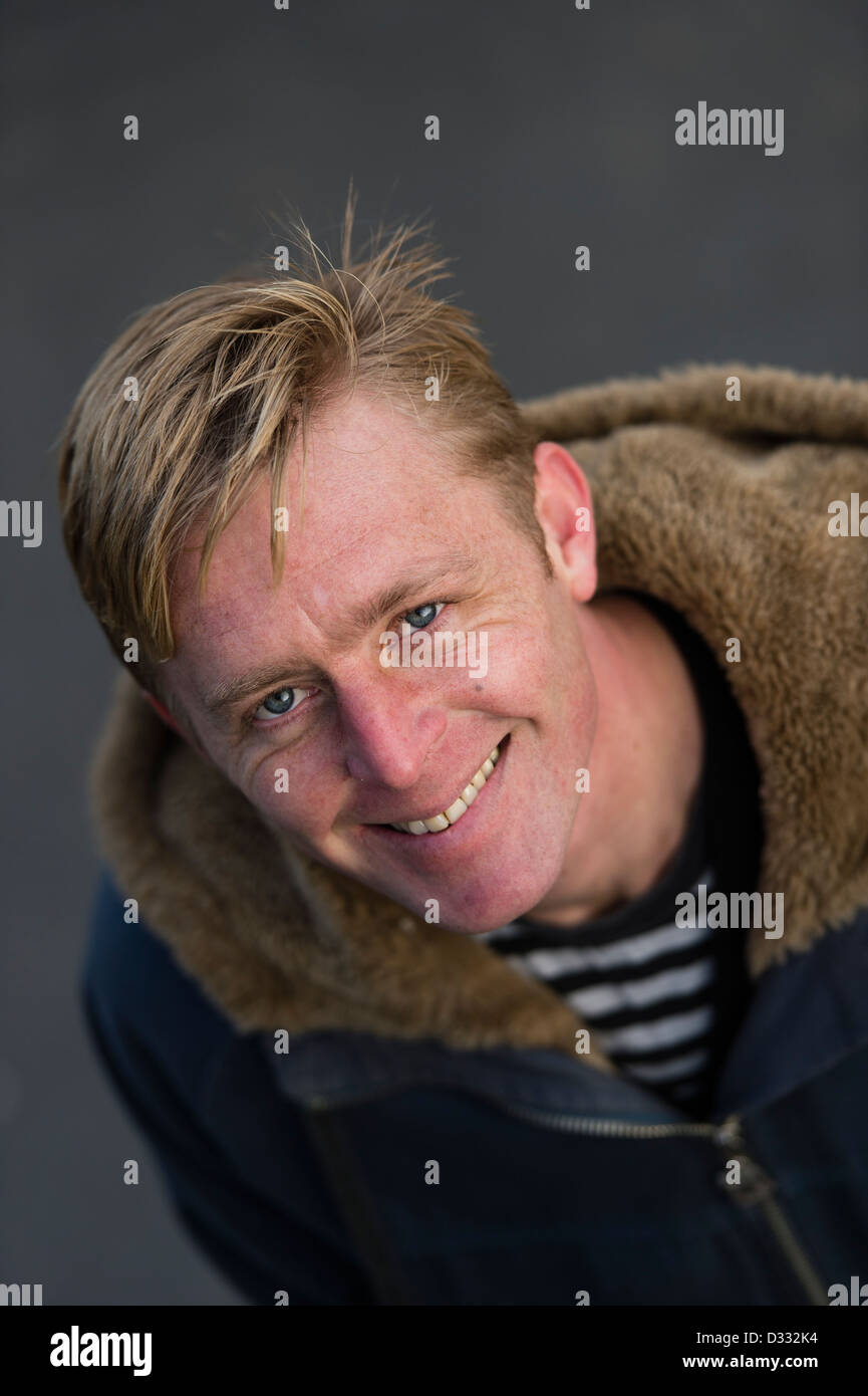 A slim blonde man male, late 30's / early 40's, single solo alone, smiling happy confident, UK - Stock Image