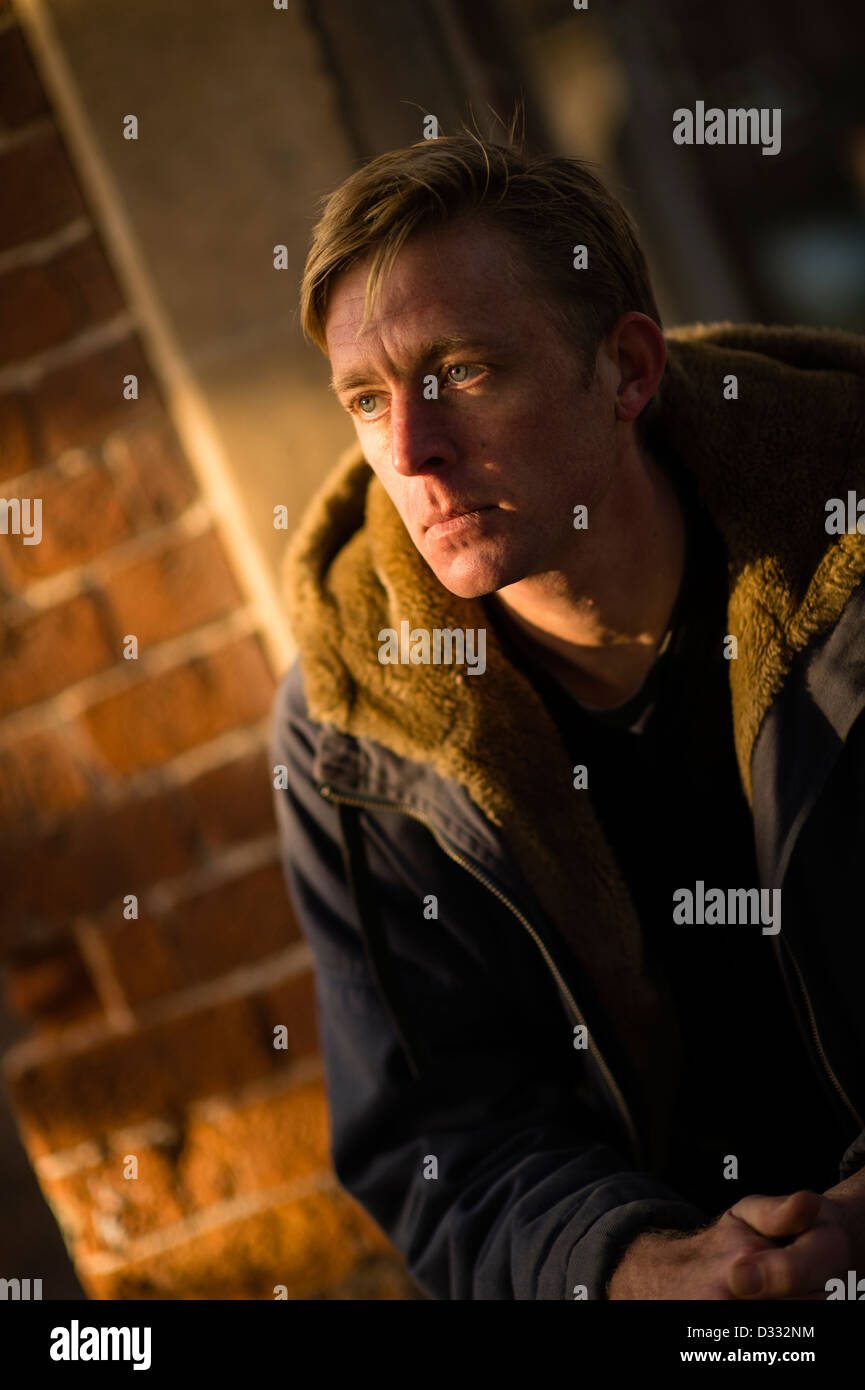 A slim blonde man male, late 30's / early 40's, single solo alone, looking sad UK - Stock Image