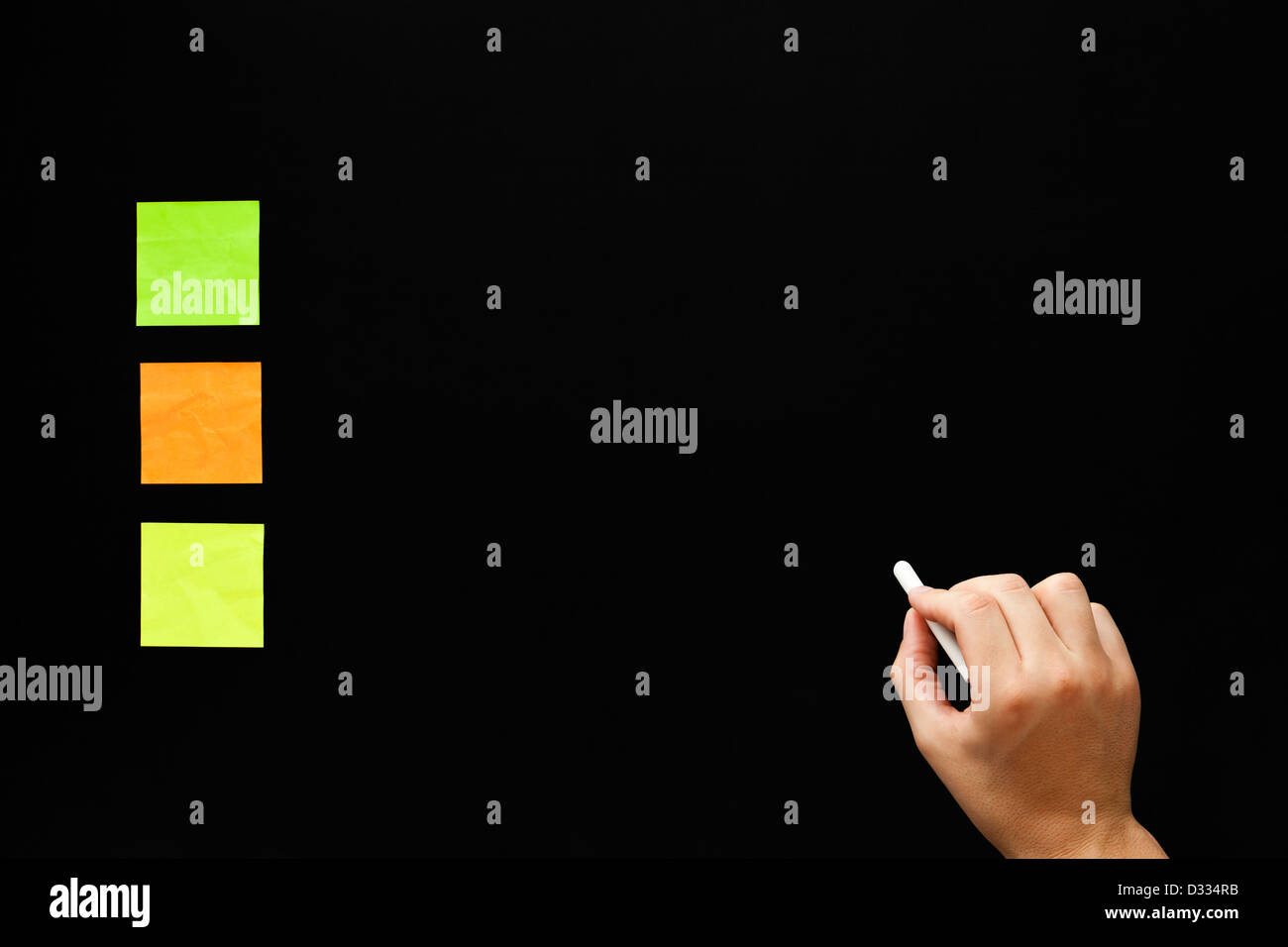 Hand writing something on blank blackboard with three different color sticky notes. - Stock Image