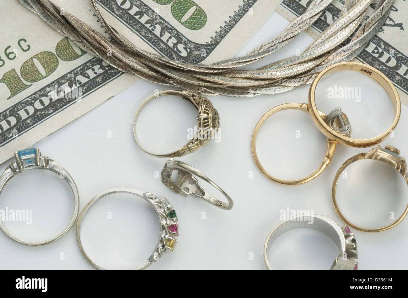 Silver, gold and white gold jewelry that is exchanged for top dollar prices, implied by 100 dollar bills on the - Stock Image