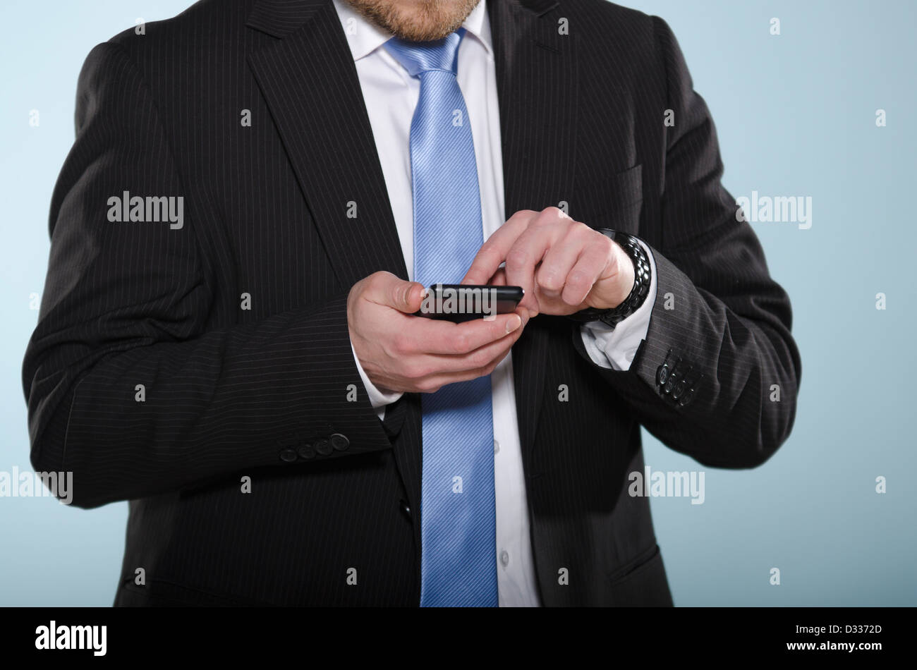 Businessman using smartphone. Middle section of casually suited man using a touch screen phone with his finger. - Stock Image