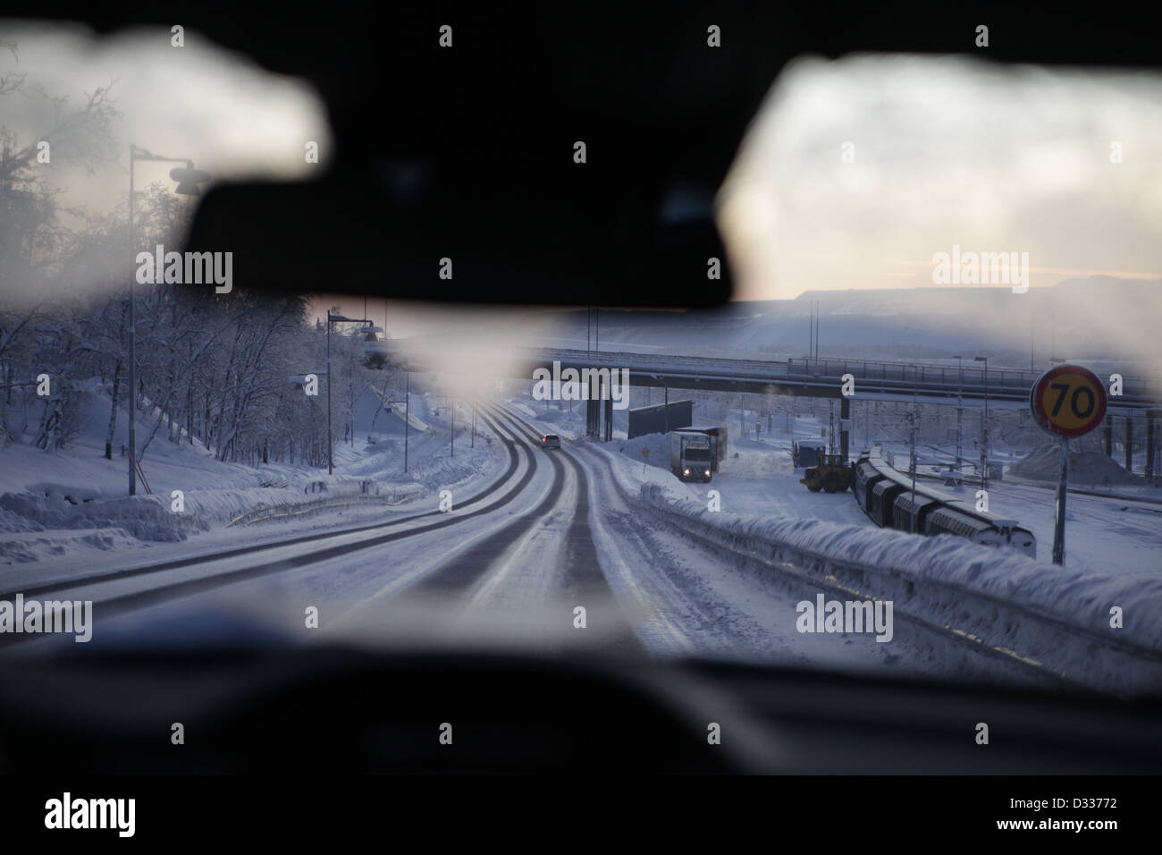 Road covered in snow and ice taken from inside car. - Stock Image