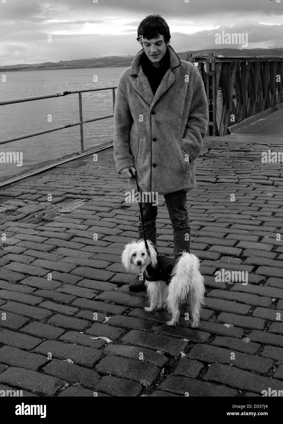 A young man, dressed in the style of a mod, stands with a small Chinese Crested dog on a harbour in the Scottish - Stock Image