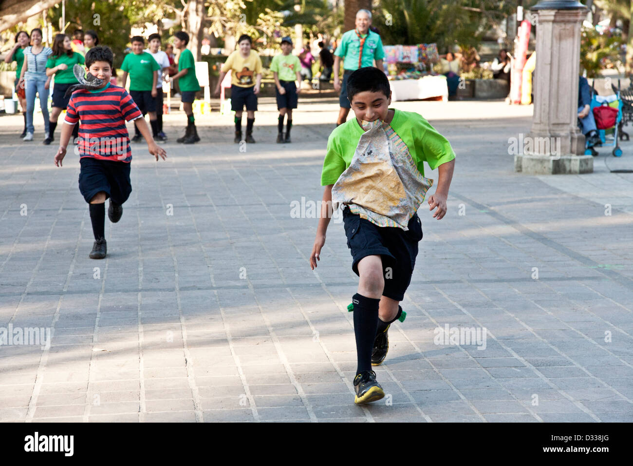 smiling tween boy scouts with handkerchiefs in their mouths running in team relay race Llano park Oaxaca de Juarez - Stock Image