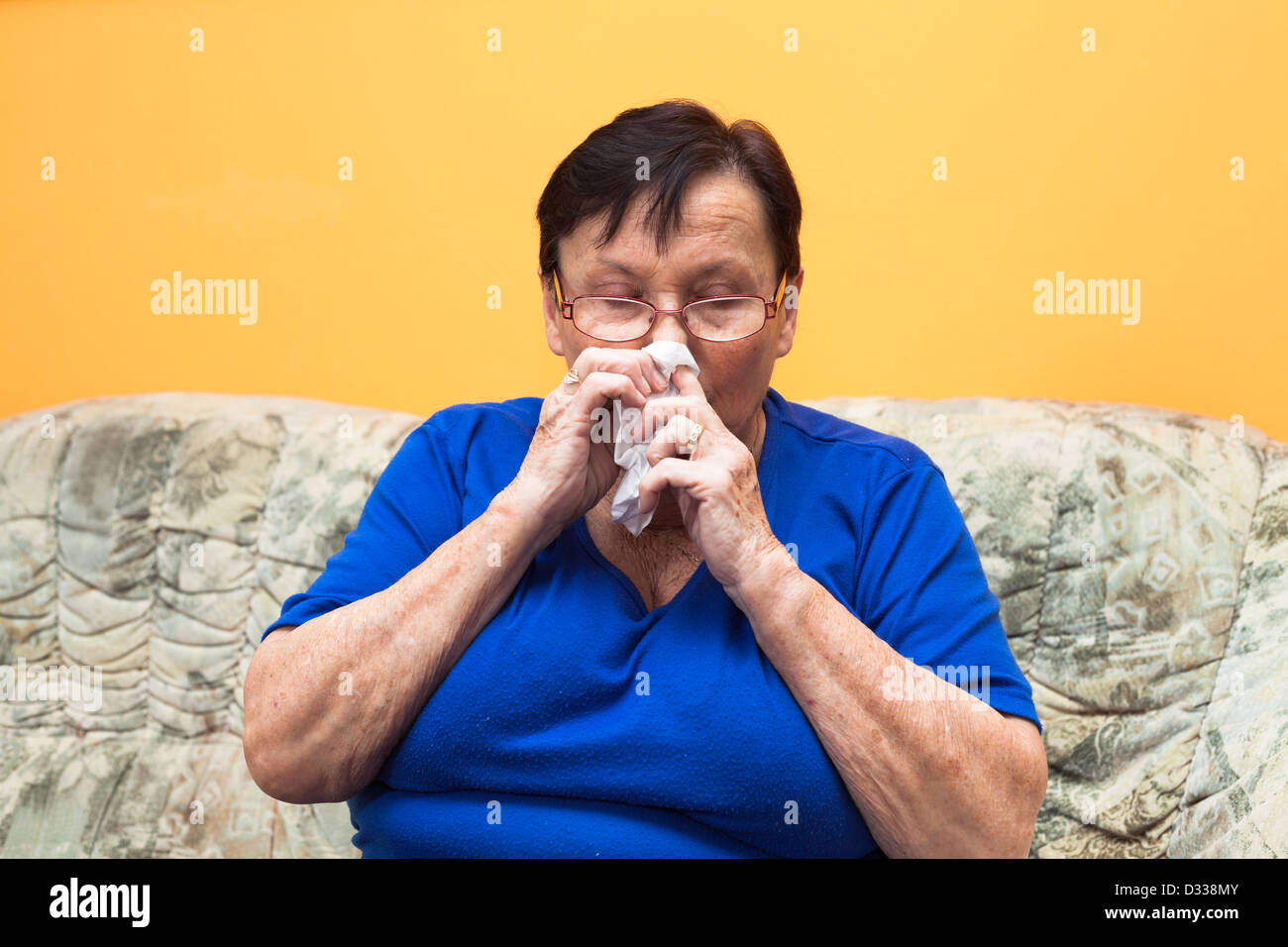 Sick senior woman sitting on sofa and blowing her nose. - Stock Image