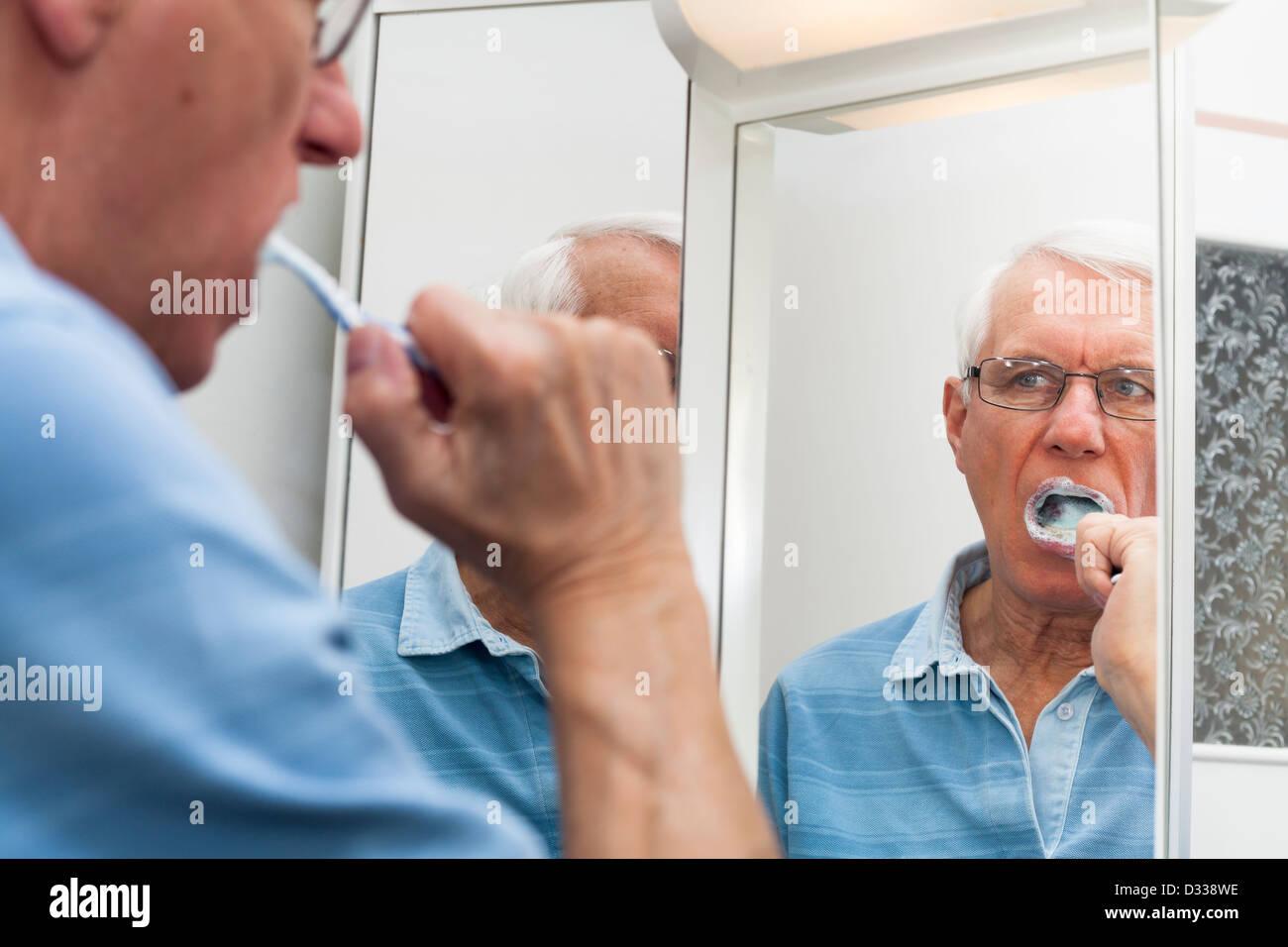 Close up of senior man reflected in mirror brushing his teeth. - Stock Image