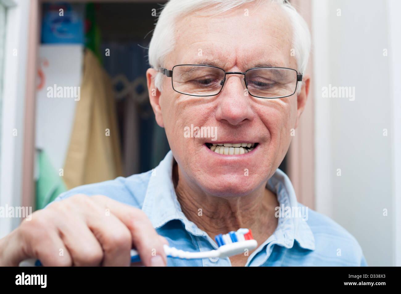 Close up of senior man going to brush his teeth. - Stock Image