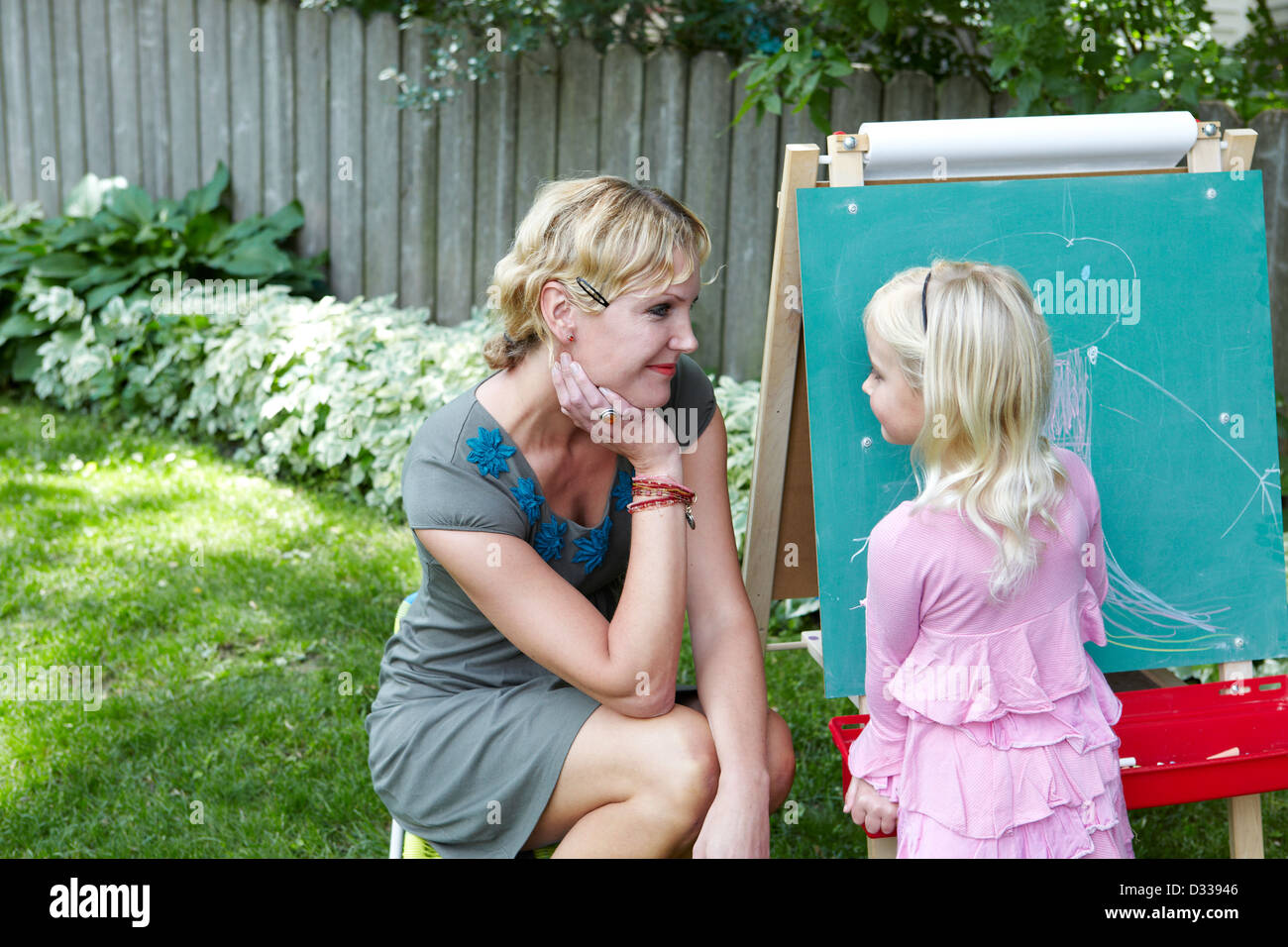 Mother and daughter drawing in the garden - Stock Image