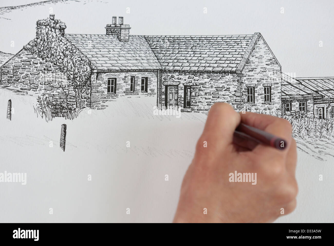 Artist drawing sketching in studio pen and ink line drawing of old scottish cottage architecture in orkney islands