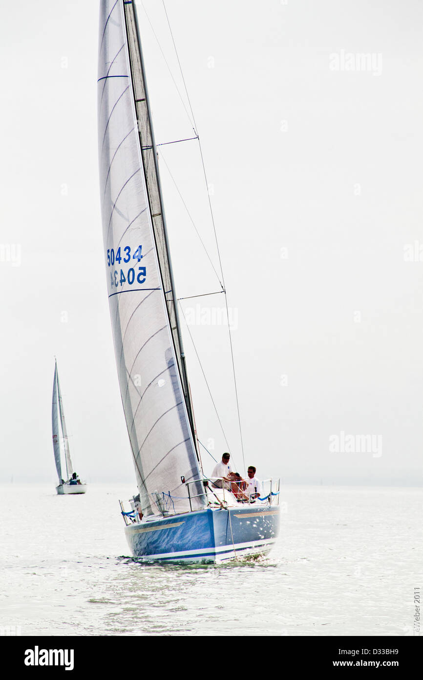 Two men sail IMX 38 sail boat with sun dappled blue hull in gentle breeze on Lake Erie off the coast of Cleveland, - Stock Image