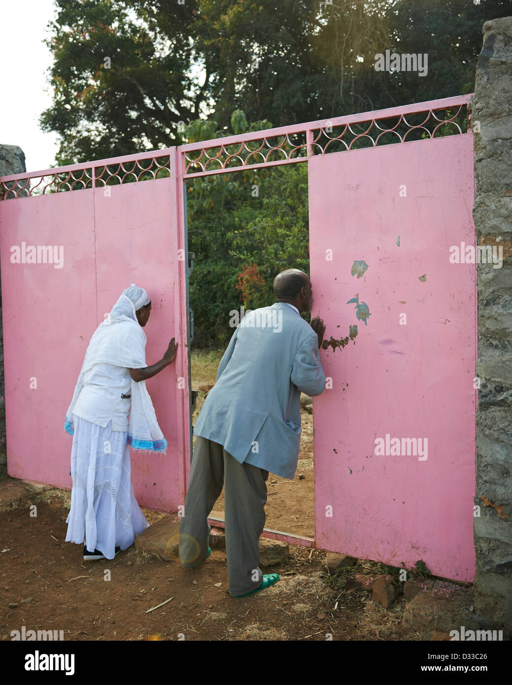 Pilgrims from the Ethiopian Orthodox Church journey to the Zara Church Forest and kiss the gate to pay their respect - Stock Image