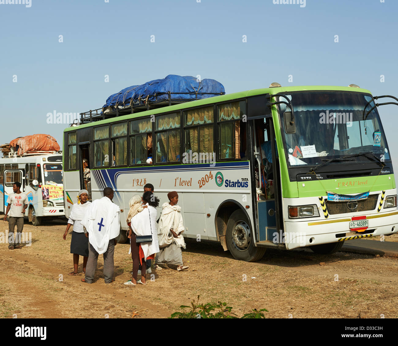Pilgrims talk to a priest outside the caravan bus at the Zara Church Forest in Ethiopia - Stock Image