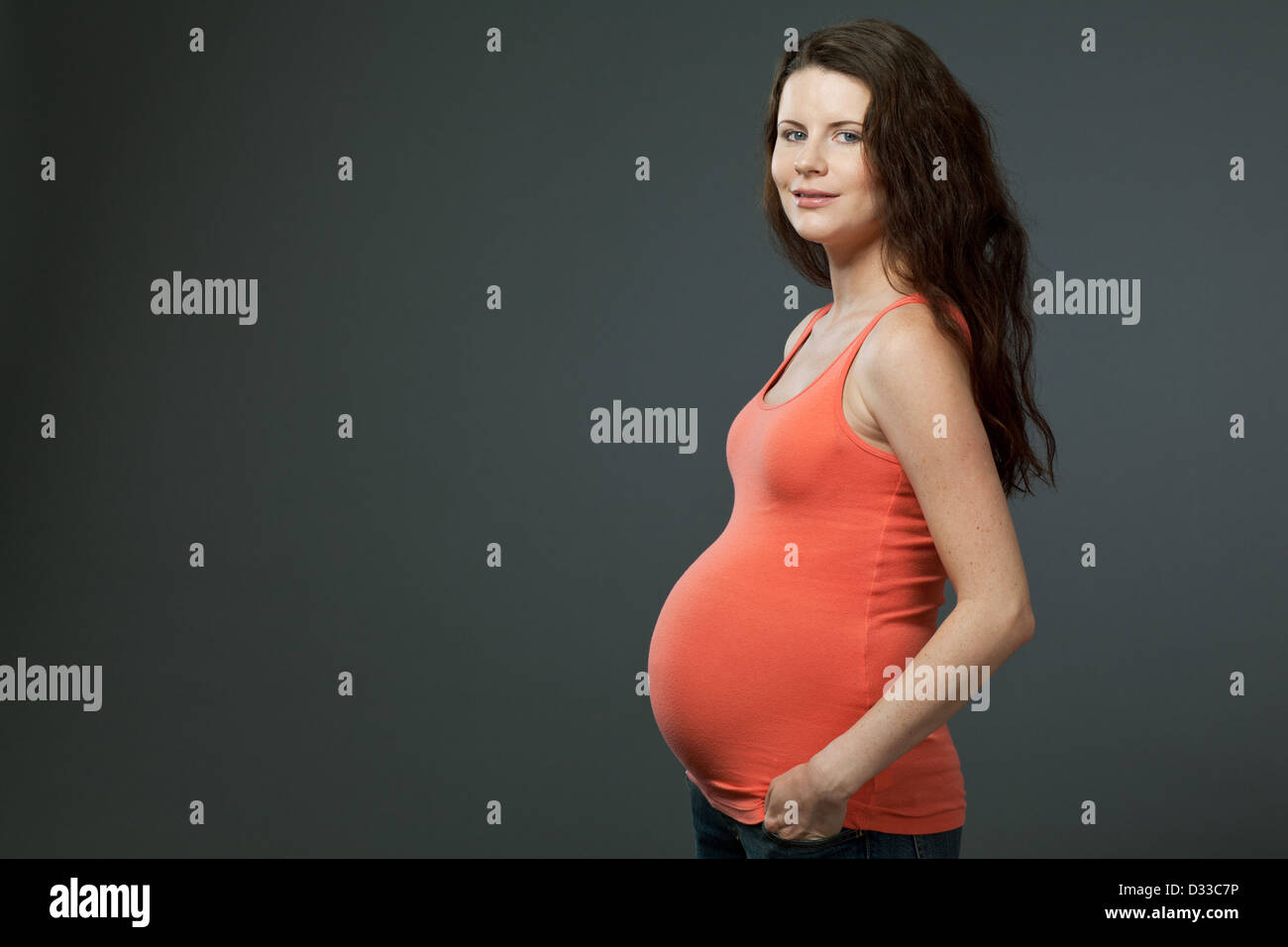 Beautiful young expecting mother with long dark hair. - Stock Image