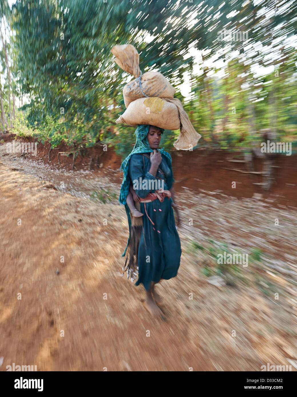 A women carrying groceries on her head from the market walking down a dirt path - Stock Image