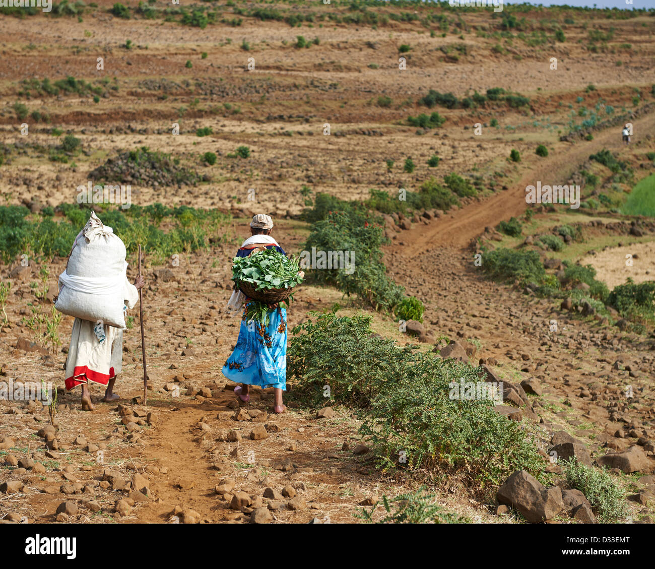 Local villagers carrying supply packs going to the market on a dirt path - Stock Image