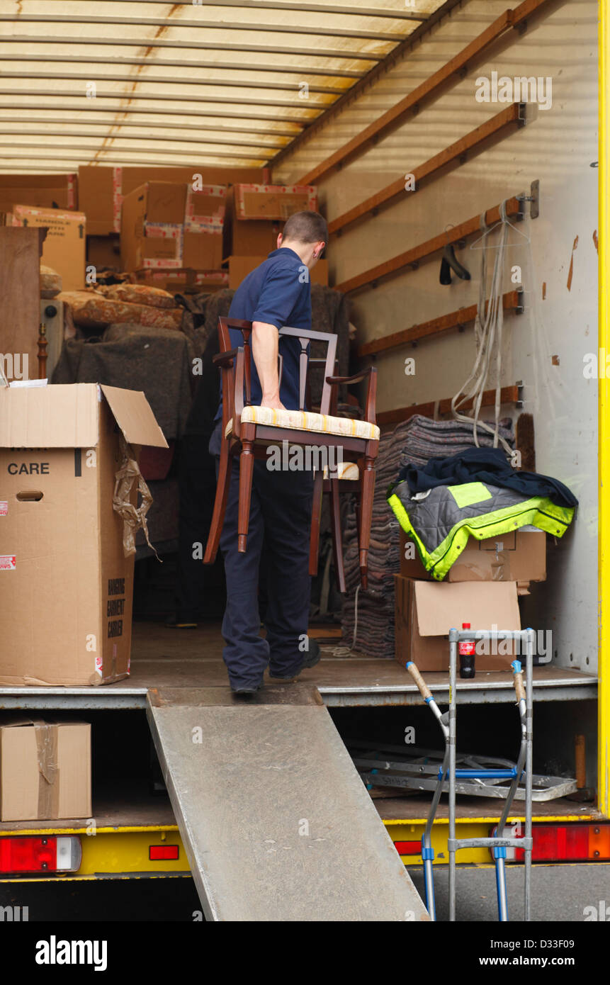 Removal men carrying furniture into a removal van. Stock Photo