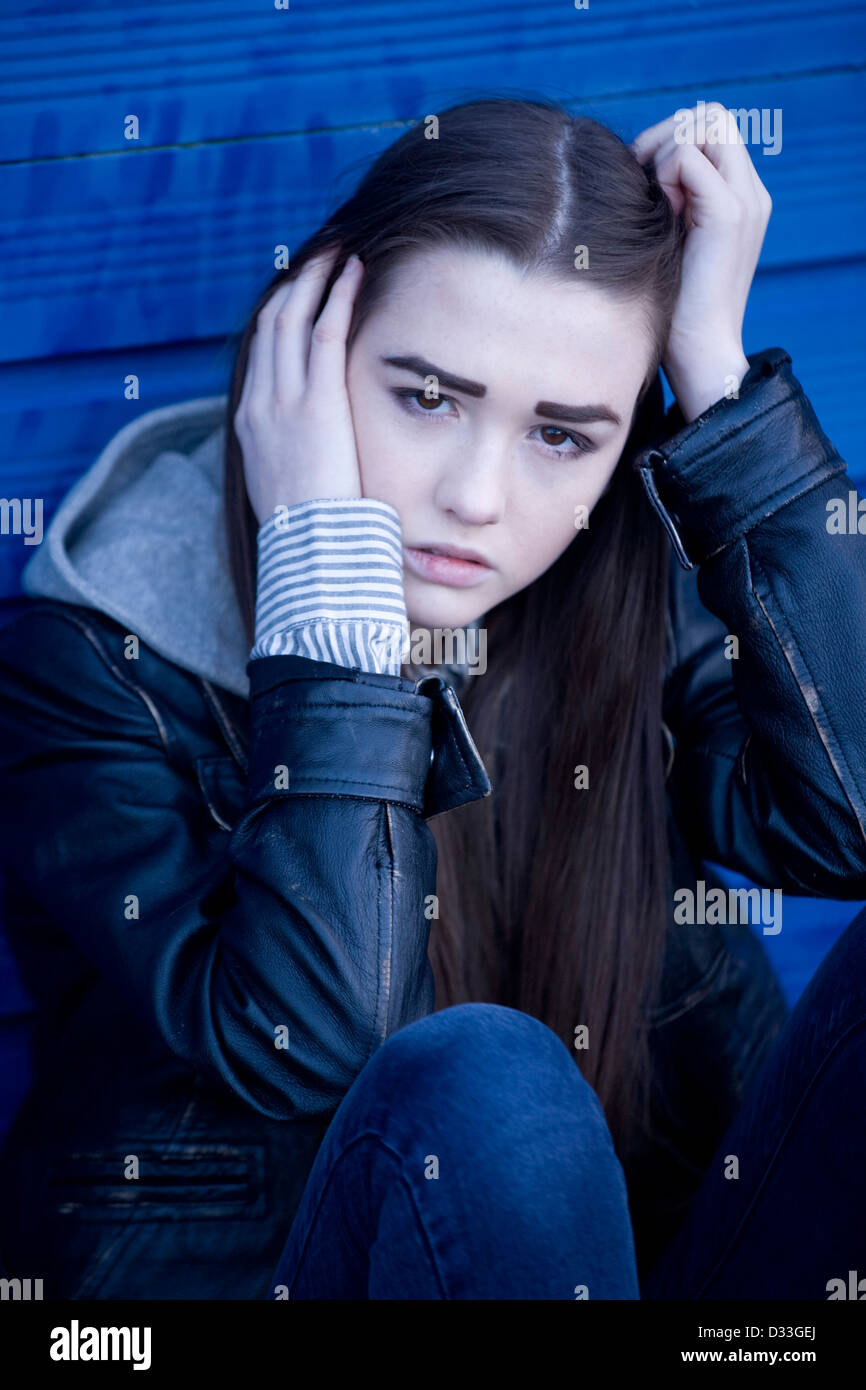 A troubled young teenage girl sitting outside. - Stock Image