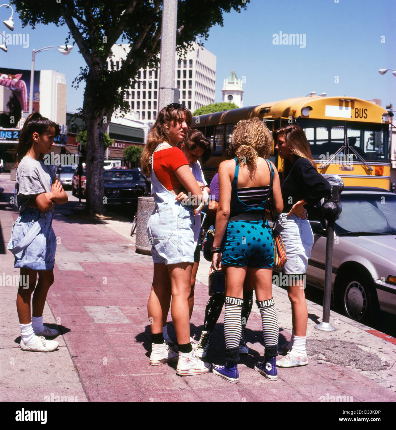 Archival Photo Of Group Teenage High School Girls 1980s Or 1990s Standing In The Street With A Yellow American Bus Westwood Village Los Angeles