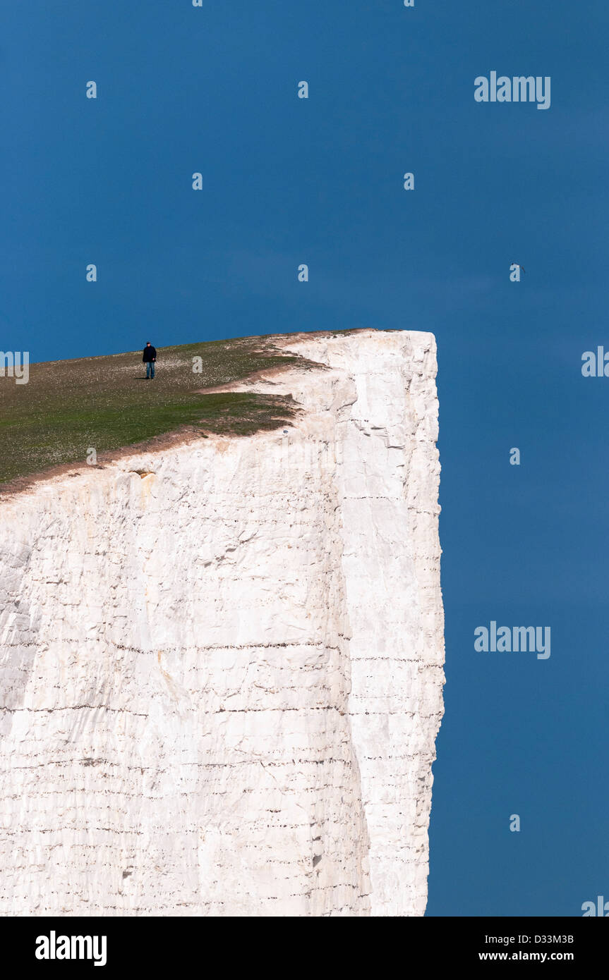 Man walking close to the edge of the sheer cliffs at Beachy Head in East Sussex, England, UK - Stock Image