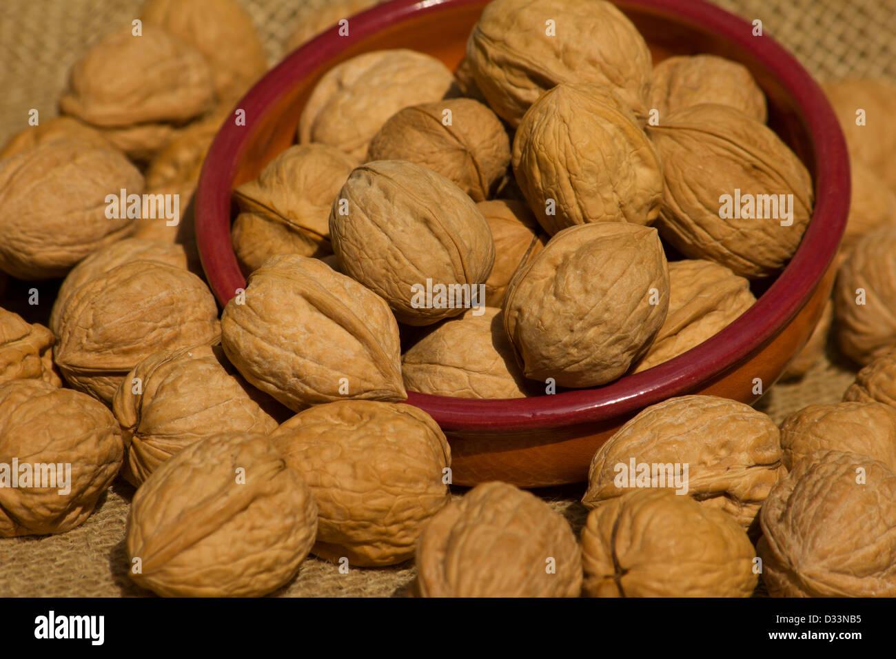 Walnuts in a ceramic bowl on burlap Stock Photo
