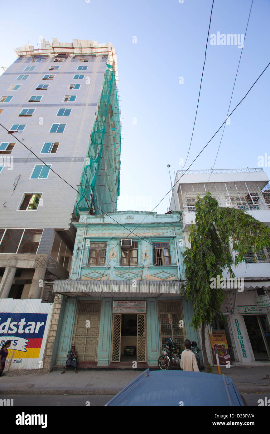 1930s indian building towered over by new hi-rise construction, Dar es Salaam, Tanzania. - Stock Image