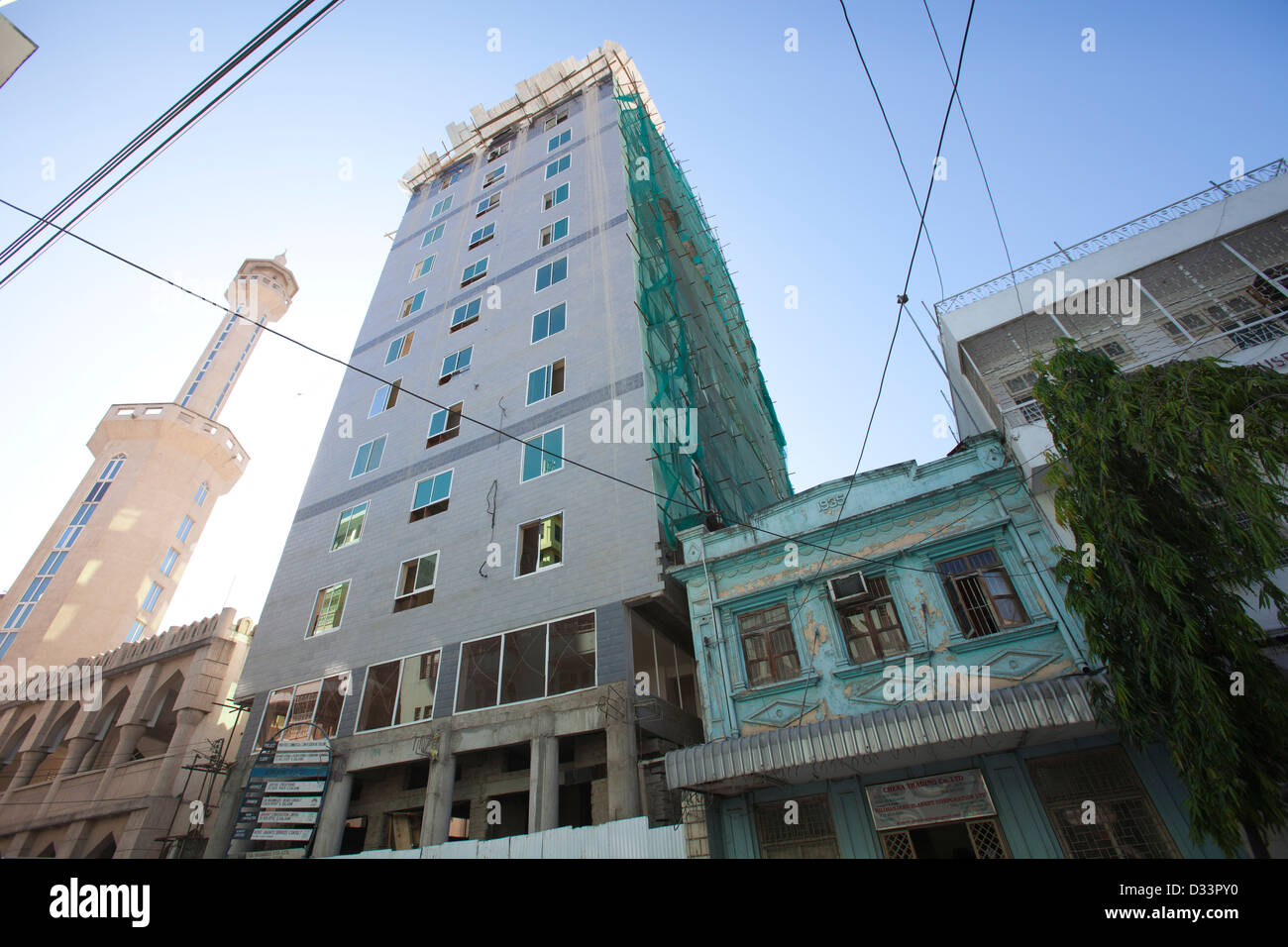 Hi-rise building under construction, next to a 1930s Indian building and Mosque, Dar es Salaam, Tanzania. - Stock Image