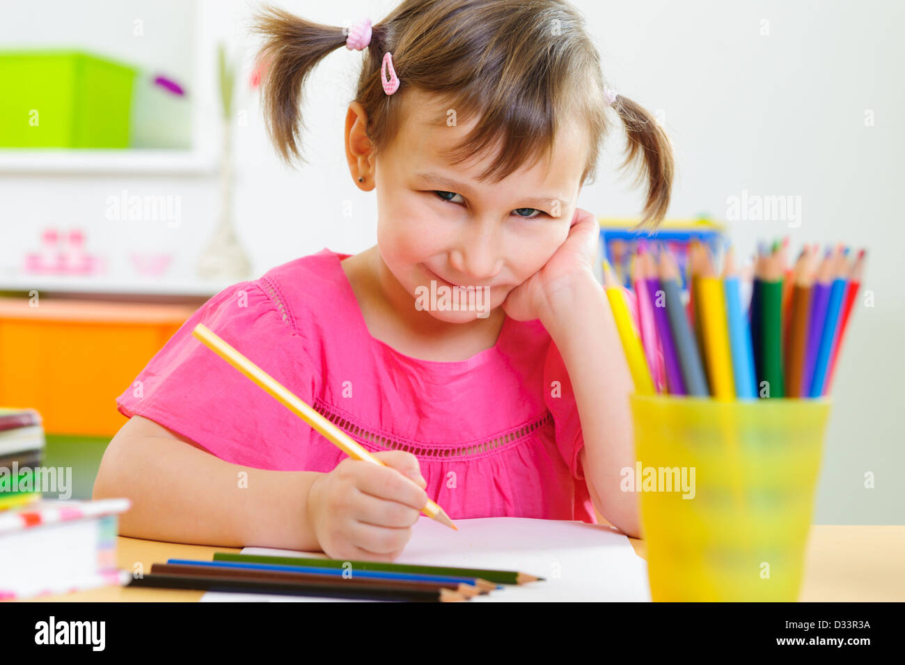 Cute little girl drawing with pencils at home - Stock Image