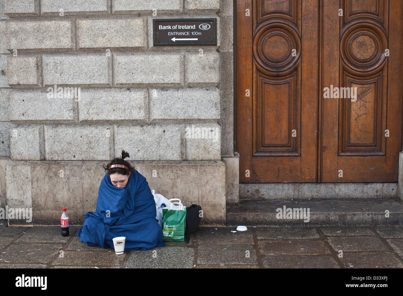 Homeless woman begging on the doorstep of the Bank of Ireland, Westmoreland Street, Dublin, Ireland. - Stock Image