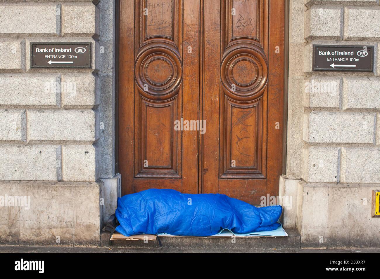 Homeless woman sleeping on the doorstep of the Bank of Ireland, Westmoreland Street, Dublin, Ireland. - Stock Image