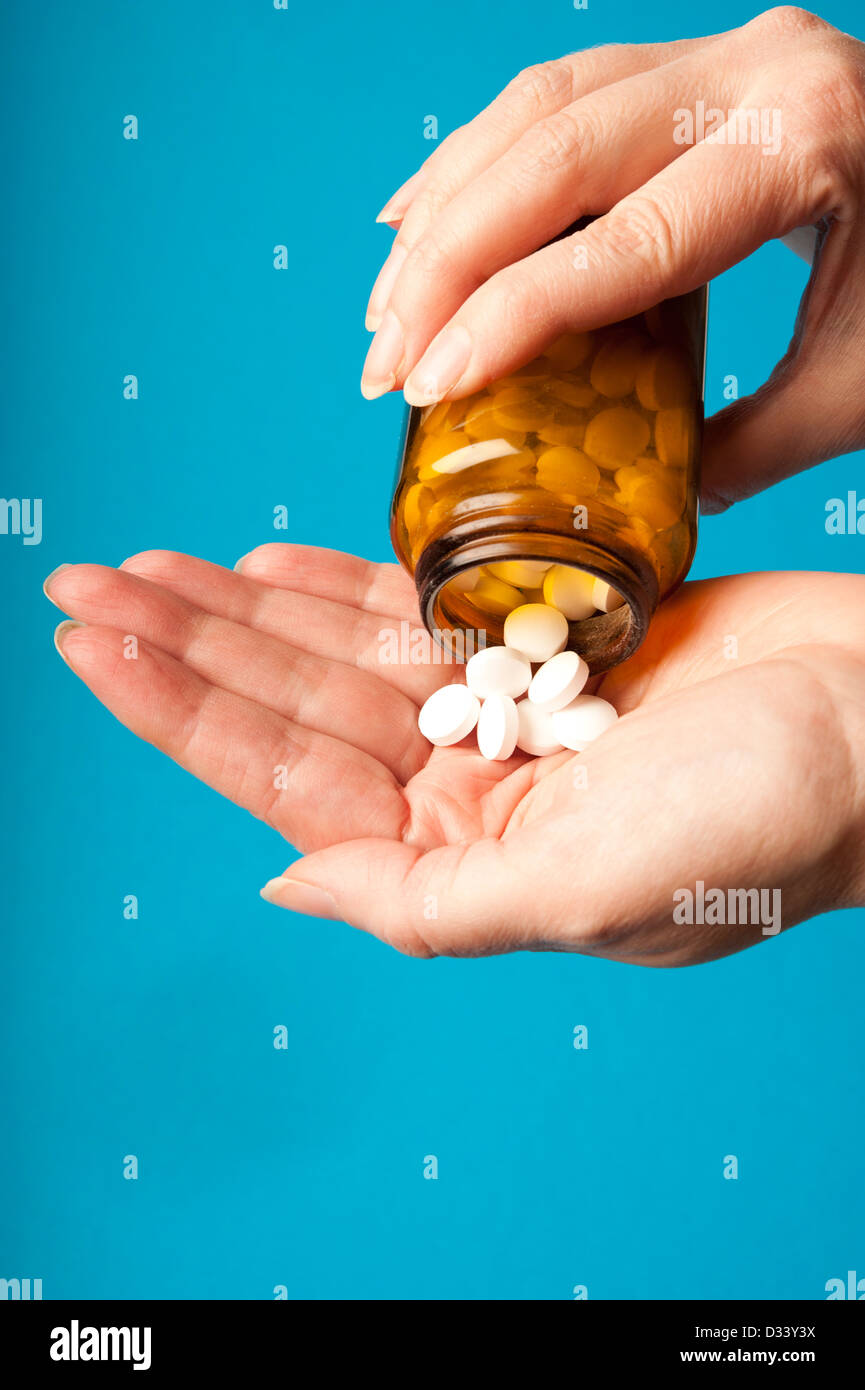woman pouring pills from a medicine bottle into her hand - Stock Image