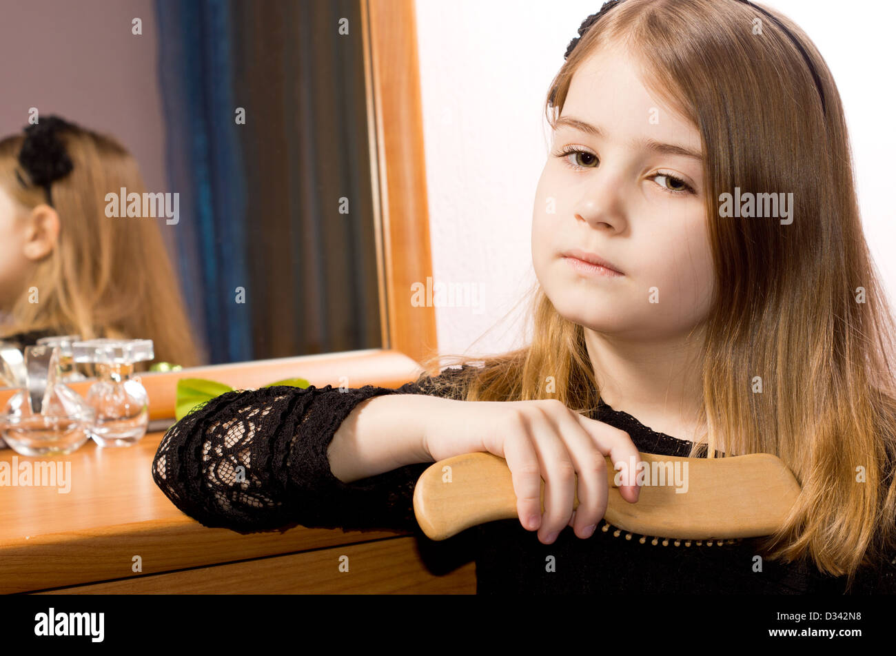 Sad pretty little girl brushing her long blonde hair with a hairbrush reflected in the mirror of the dressing table - Stock Image