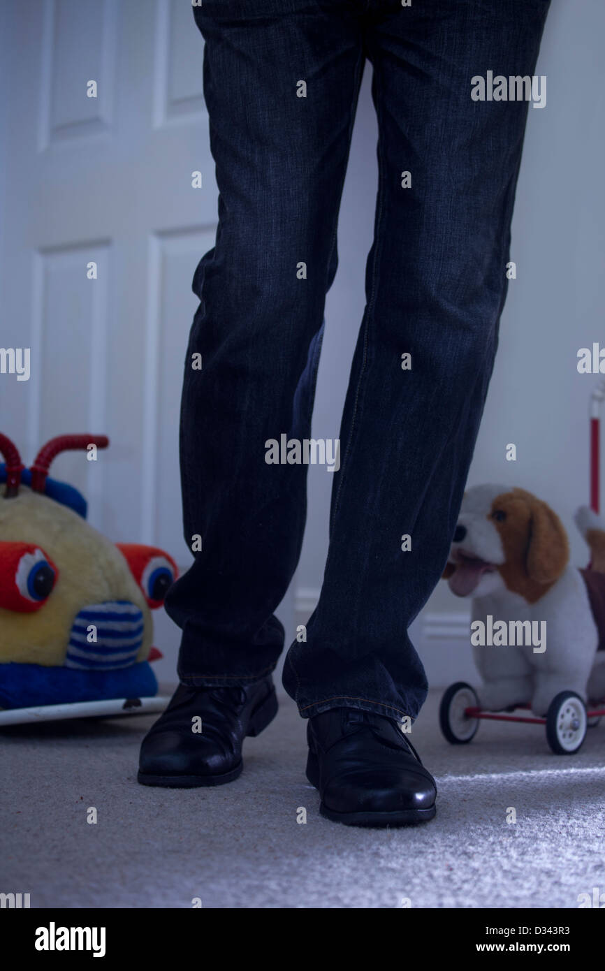 Male legs walking into a darkly lit child's bedroom with a door, toy car and toy dog in the background. - Stock Image